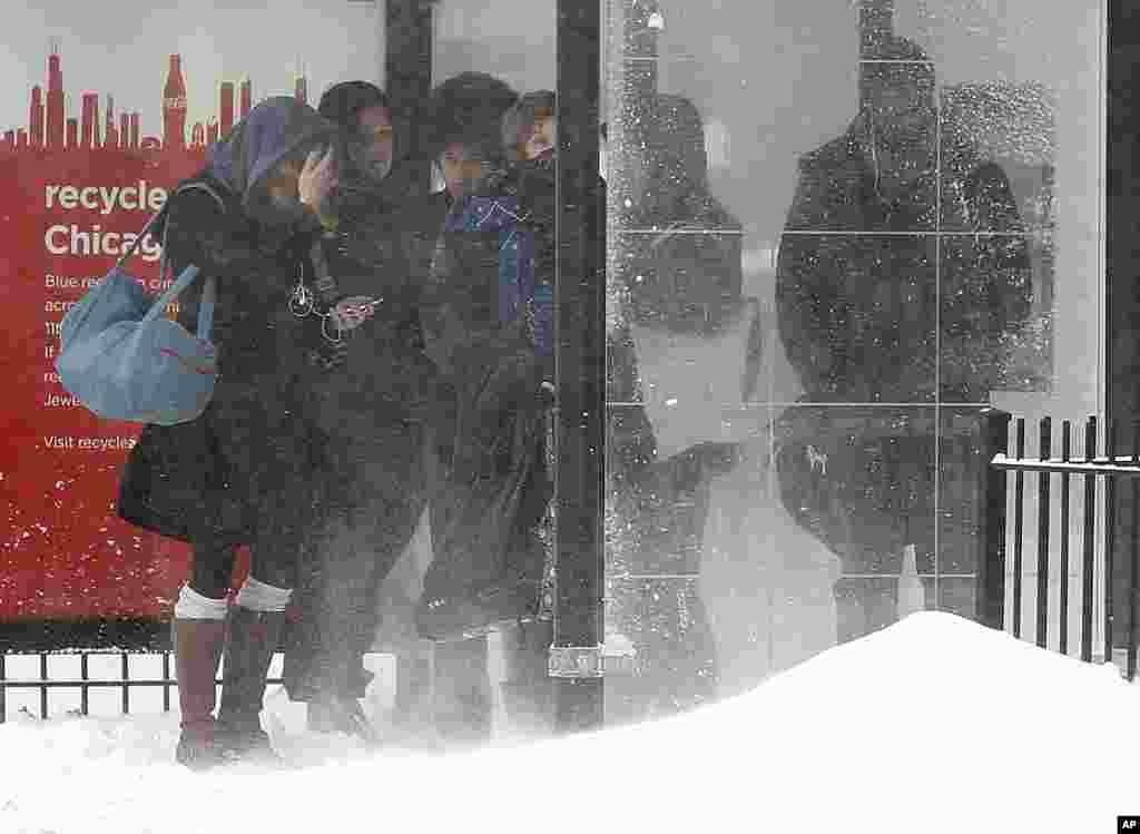 Những người đi làm chờ xe buýt của họ trong tuyết bay ở Chicago, Illinois. Tuyết bay nặng di chuyển ngang hầu hết Illinois khi tiểu bang này gặp phải vòng thời tiết mùa đông mới nhất.