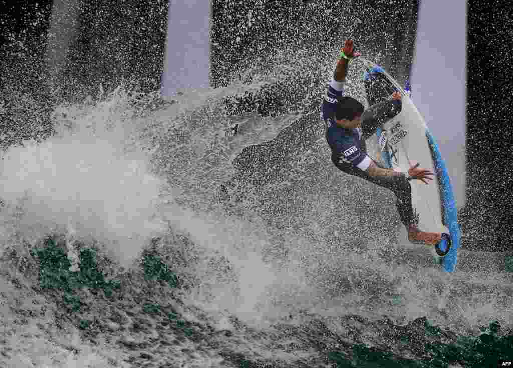 Alex Ribeiro of Brazil competes beside the pier during round four of the Vans US Open of Surfing,  held at iconic Huntington Beach, California.