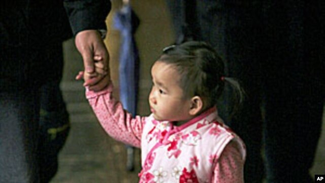 A young boy holds his sister as their family prays at a local temple. Taiwanese official has urged citizens to procreate amid fears the Year of the Tiger may bring reduced reproduction on the island already with one of the world's lowest birth rates, (Fil