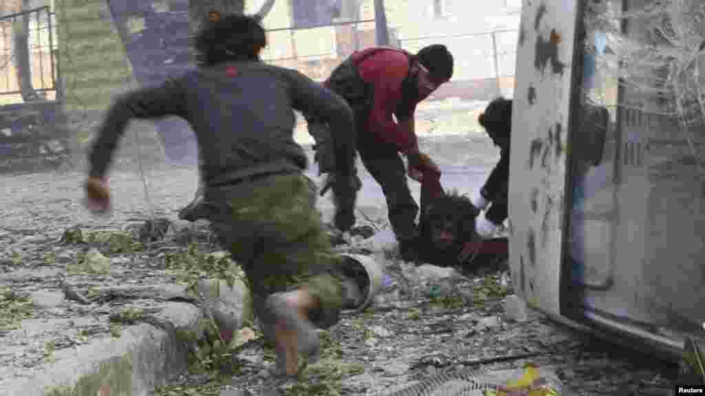 Free Syrian Army fighters rush to help their fellow fighter after he was shot by a sniper.