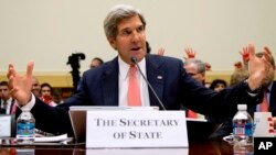 El secretario de Estado, John Kerry habla en la Cámara de Representantes, mientras en el fondo se elevan manos rojas de manifestantes opuestos a un ataque militar en Siria.