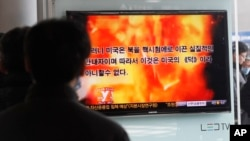 People watch a television program showing a propaganda video released by North Korea at Seoul Railway Station in Seoul, South Korea, February 20, 2013.