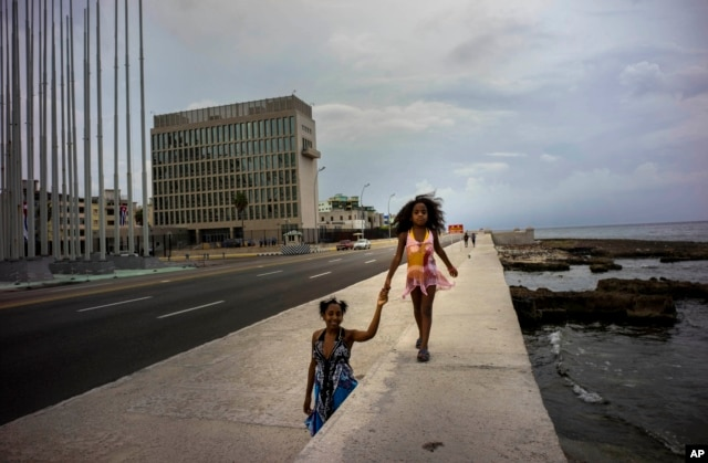 A girls holds her mother's hand, as she walks on the Malecon sea wall, past the the US embassy in Havana, Cuba, Aug. 11, 2015.