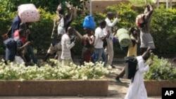 Civilians flee with their belongings in Abidjan, Ivory Coast, April 5, 2011