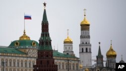 A Russian national flag is seen atop of the Grand Kremlin Palace in Moscow, Russia, March 18, 2014