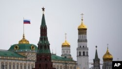 A Russian national flag is seen atop of the Grand Kremlin Palace an hour before Russian President Vladimir Putin addressed the Federal Assembly in the Kremlin in Moscow, Tuesday, March 18, 2014