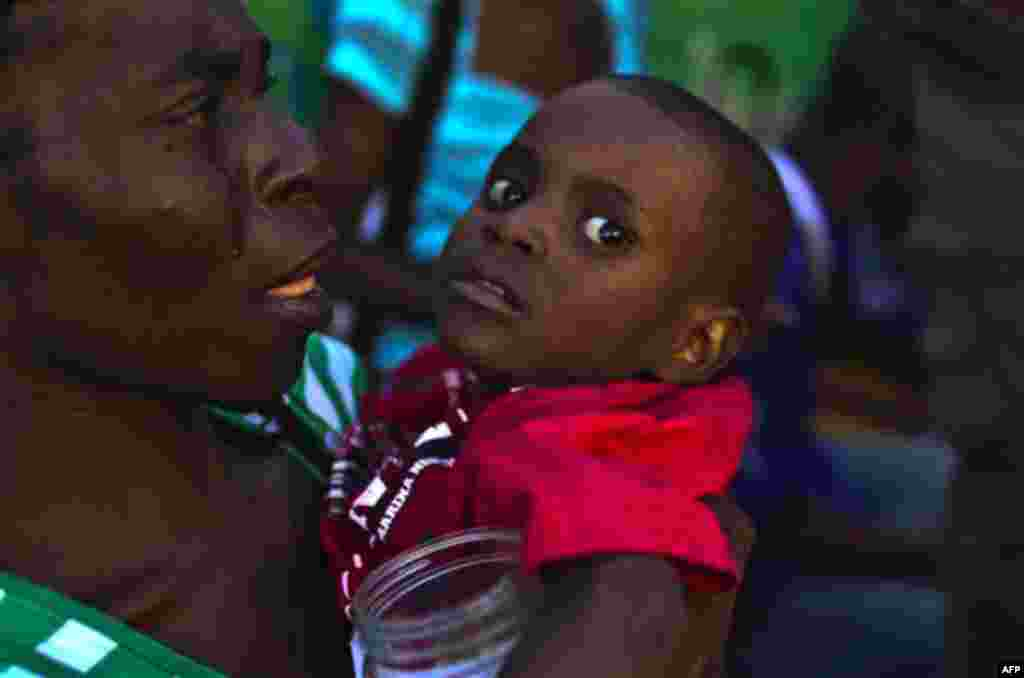 A woman carries a child with symptoms of cholera at the entrance of the St. Catherine hospital in the Cite Soleil neigborhood in Port-au-Prince, Haiti,Thursday, Nov. 11, 2010. Nearly 11,000 people people have been hospitalized for cholera across Haiti wit