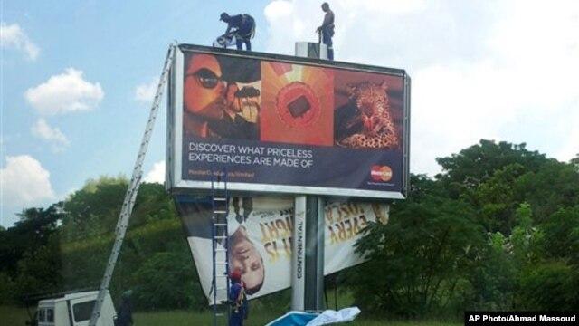 Pekerja tampak menurunkan papan reklame yang memuat wajah atlet Olimpiade Oscar Pistorius di pinggir jalan  Johannesburg (14/2/2013).