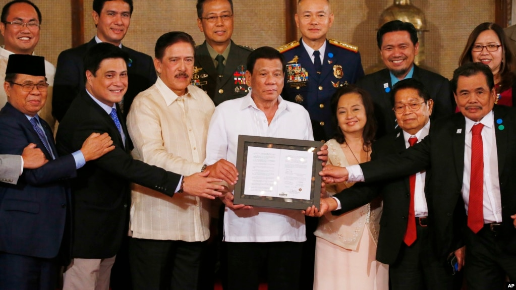 "FILE - President Rodrigo Duterte, center, and leaders of the Moro Islamic Liberation Front, including Al Haj Murad Ebrahim, left, Mohagher Iqbal, right, and Ghadzali Jaafar, second from right, hold together the signed ""Organic Law for the Bangsamoro Autonomous Region in Muslim Mindanao"" during a presentation at Malacanang Palace in Manila, Philippines, Aug. 6, 2018."