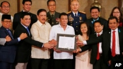 "FILE - President Rodrigo Duterte, center, and leaders of the Moro Islamic Liberation Front, including Al Haj Murad Ebrahim, left, Mohagher Iqbal, right, and Ghadzali Jaafar, second from right, hold together the signed ""Organic Law for the Bangsamoro Autonomous Region."