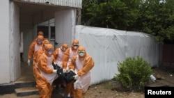 Des fossoyeurs sortant du Port Loko District Hospital en Sierra Leone (Reuters)