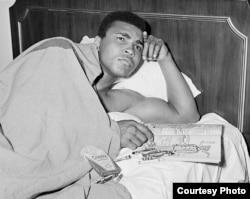 រូបលោក Muhammad Ali និងសៀវភៅគូរពណ៌មួយក្បាលស្តីពីមន្ត្រីយោធា ក្នុងអំឡុងពេលដែលលោក Ali កំពុងគិតពិចារណាអំពីការឆ្លើយតបរបស់លោកទៅនឹងសេចក្តីប្រកាសបិទសិទ្ធិប្រដាល់របស់លោក កាលពីឆ្នាំ១៩៦៧។ (រូបថតផ្តល់ឲ្យដោយ George Kalinsky)