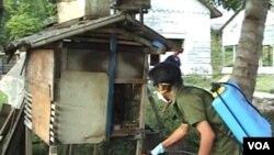 Petugas melakukan penyemprotan kandang ternak milik warga Poso (foto:dok).