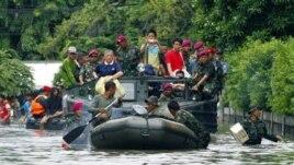 Para anggota marinir melakukan evakuasi beberapa warga yang terjebak banjir di Jakarta, Minggu (20/1).
