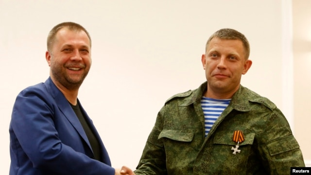"Aleksander Borodai (L), leader of the self-proclaimed ""Donetsk People's Republic"" shakes hands with rebel leader Aleksander Zakharchenko, during their news conference in Donetsk August 7, 2014."