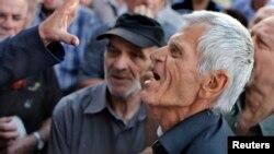 2015年7月6日领取退休金希腊老人试图进入雅典国家银行分行时和官员争论