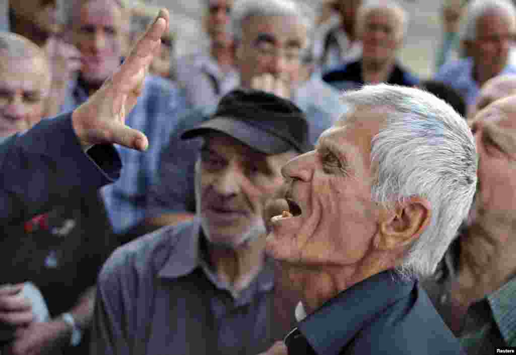 A pensioner argues with an official as he tries to enter a National Bank branch to receive part of his pension in Athens, Greece, July 6, 2015.