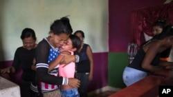 Feliana Márquez, la hija de 13 años de Daniel Márquez, uno de los prisioneros muertos en un motín e incendio en una cárcel de Carabobo, Venezuela, es consolada por su tía Sorangel Gutiérrez, después que el cuerpo de Daniel fue traído a la casa de la familia en Valencia, para su funeral. Marzo 29 de 2018.