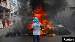 រូបឯកសារ៖ បាតុករម្នាក់ដែលពាក់អាវយឺតមានសរសេរអក្សរថា «ជីវិតមនុស្សគ្រប់រូបគឺសំខាន់» ចូលរួមធ្វើបាតុកម្មទាមទារឲ្យប្រធានាធិបតីហៃទីលោក Jovenel Moise ចុះចេញពីតំណែង នៅទីក្រុង Port-au-Prince ប្រទេសហៃទី កាលពីថ្ងៃទី១៥ ខែមករា ឆ្នាំ២០២១។