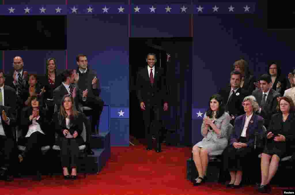 صدر براک اوباما مباحثے میں شرکت کے لیے ہال میں داخل ہورہے ہیں