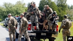 Law enforcement officers get off a truck to search for David Sweat and Richard Matt, who escaped from the Clinton Correctional Facility, in a wooded area in Schuyler Falls, New York, June 14, 2015.