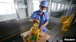 2018年7月4日,在中國山東省曲阜市,在糧油工業和進出口公司的工廠,工人把瓶裝大豆油裝箱,這些大豆油是用美國大豆製造的。