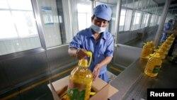中国山东省曲阜市,粮油工业和进出口公司的工人把瓶装大豆油装箱,这些大豆油由美国大豆制造(2018年7月4日)。美国农业部周四表示,中国已经开始恢复购买美国大豆。