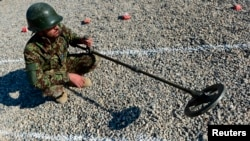 FILE - An Afghan soldier uses a mine detector during a demining drill at Camp Shaheen, a training facility for the Afghan National Army (ANA), west of Mazar-i-Sharif, Dec. 13, 2014.