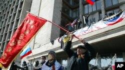 4月7日在乌克兰东部的顿涅茨克,活动人士在一座政府办公楼前挥舞前苏联和俄罗斯的国旗