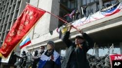 在乌克兰的顿涅茨克地区政府门前的路障旁,活动分子会晤前苏联的旗帜和俄罗斯国旗