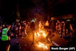 Demonstran membakar sampah di Oakland, California, pada 29 Mei 2020, memprotes kematian George Floyd. (Foto: A /Noah Berger)