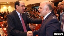 Iraq's Vice President Nouri al-Maliki (L) and new Prime Minister Haider al-Abadi shake hands during the session to approve the new government in Baghdad, September 8, 2014.Iraq's parliament approved a new government headed by Haider al-Abadi as prime mini