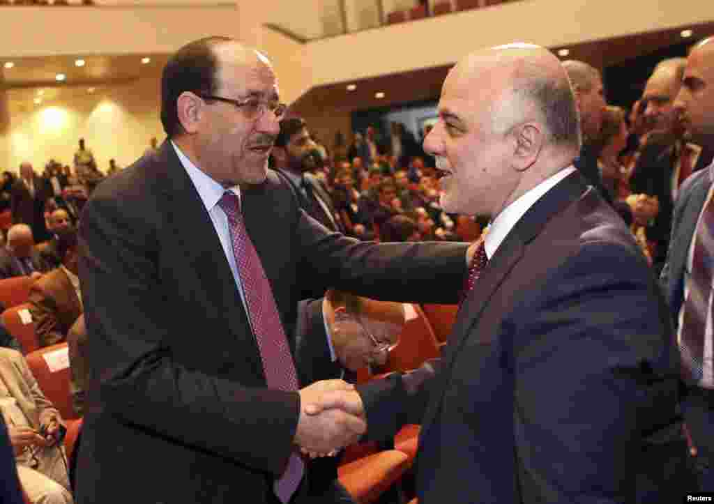 Iraq's Vice President Nouri al-Maliki (left) and incoming Prime Minister Haider al-Abadi shake hands during the session to approve the new government in Baghdad, Sept. 8, 2014.