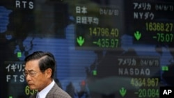 A man walks past an electronic stock board of a securities firm in Tokyo as the 225-issue Nikkei Stock Average, shown top center, dived 454.00 points, or 2.98 percent, and finished at 14,778.37, hitting a two-month low Friday, Aug. 8, 2014.