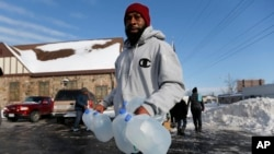 FILE - Lemott Thomas carries free water being distributed at the Lincoln Park United Methodist Church in Flint, Mich., Feb. 3, 2015. Flint's mayor has declared a state of emergency due to problems with the city's water system caused by using water from the Flint River, saying the city needs more federal help.