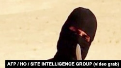 FILE - An image taken from a video released by the Islamic State group purportedly shows a masked militant holding a knife.