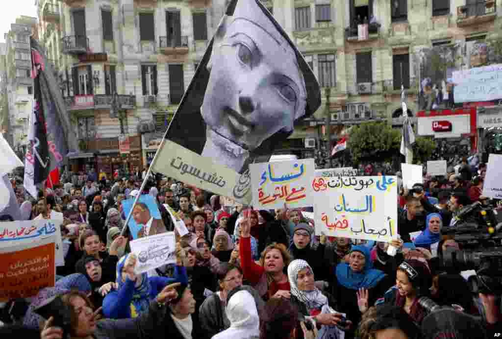 2013年3月8日,在开罗,埃及女子参加纪念国际妇女节的示威。示威者高举横幅旗帜,亮出埃及历史上唯一的女性统治者---女法老哈特谢普苏特的形象并反对穆斯林兄弟会。