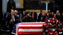 El exsenador Bob Dole, saluda el ataúd cubierto con la bandera de EE.UU. que contiene el cuerpo del expresidente George H.W. Bush y que yace en capilla ardiente en el Capitolio, en Washington. Diciembre 4 de 2018.