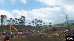 Tim gabungan kepolisian, tim SAR, TNI dan relawan mengevakuasi korban dan menerjunkan alat berat ke lokasi bencana. (VOA/R. Teja Wulan)