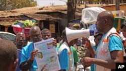 Health workers teach people about the Ebola virus and how to prevent infection, in Conakry, Guinea, March 31, 2014.