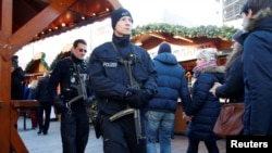 German police patrol with submachine guns at the Christmas market at Breitscheid square in Berlin, Dec. 30, 2016. An Tunisian attacker ploughed through a crowd at the market with a truck, killing at least twelve people.