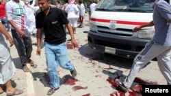 Des habitants sur le lieu d'un attentat à la bombe à Bakouba, en Irak, le 17 mai 2013