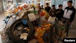 FILE - Jordanian students tour an exhibition on the amount of plastic waste in the Gulf of Aqaba and in the world's oceans in Amman, Nov. 19, 2014.