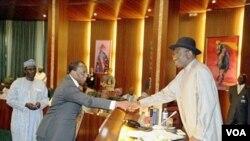 Pejabat Presiden Nigeria Goodluck Jonathan berjabat tangan dengan Menkeu Olusegun Aganga di Abuja.