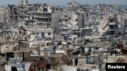 FILE - Damaged buildings are seen in the besieged area of Homs, Syria.