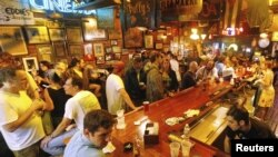 People gather in a French Quarter bar as Tropical Storm Isaac passes through New Orleans, Louisiana, August 29, 2012.