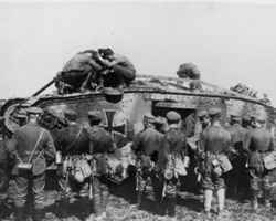 German soldiers standing around a German tank as other soldiers make repairs