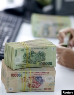 FILE - A bank employee checks Vietnamese dong banknotes at a bank in Vinh Yen city, Vietnam.
