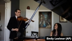 Musicians David Shenton and Erin Shields perform inside their home in the Queens borough of New York on March 30, 2021. (AP Photo/Emily Leshner)