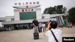 Seorang turis China berpose untuk foto di perbatasan antara China dan Korea Utara, di Hunchun, provinsi Jilin, 29 Agustus 2011. (Foto: dok).